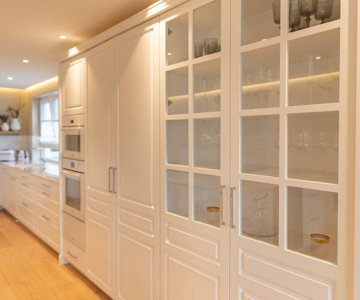 Küchenschränke mit Glasvitrine und integriertem Backofen und Mikrowelle.
