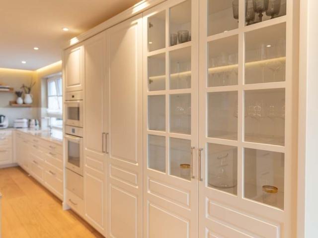 Küchenfront in weiß mit Glasvitrine und integriertem Backofen.
